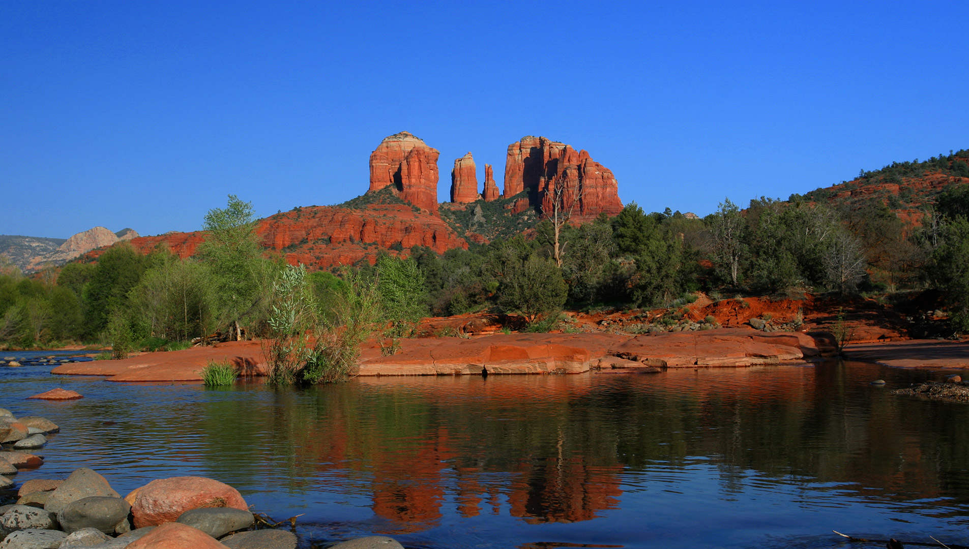The tranquil waters of Oak Creek meander through Red Rock Crossing, while Cathedral Rock looms in the background