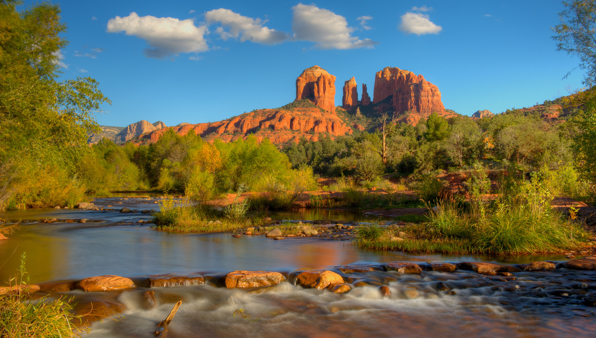 Soaring red rock bluffs rise from the placid water of Oak Creek in Sedona's Red Rock country.
