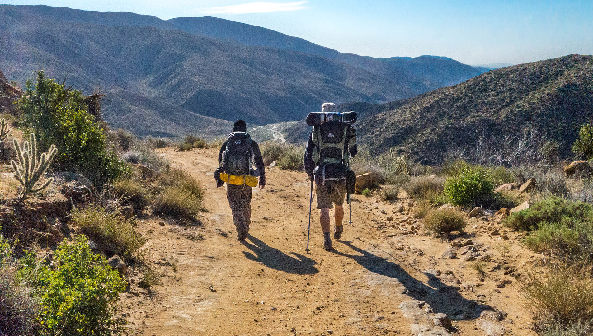 Two backpackers hike down the Juan Bautista de Anza National Historic Trail.