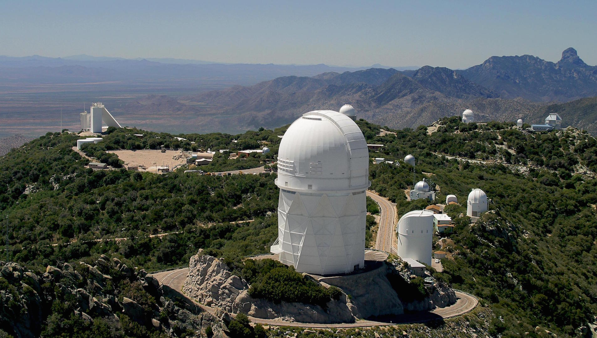 White domes and optical telescopes on the mountain peaks above the desert below.