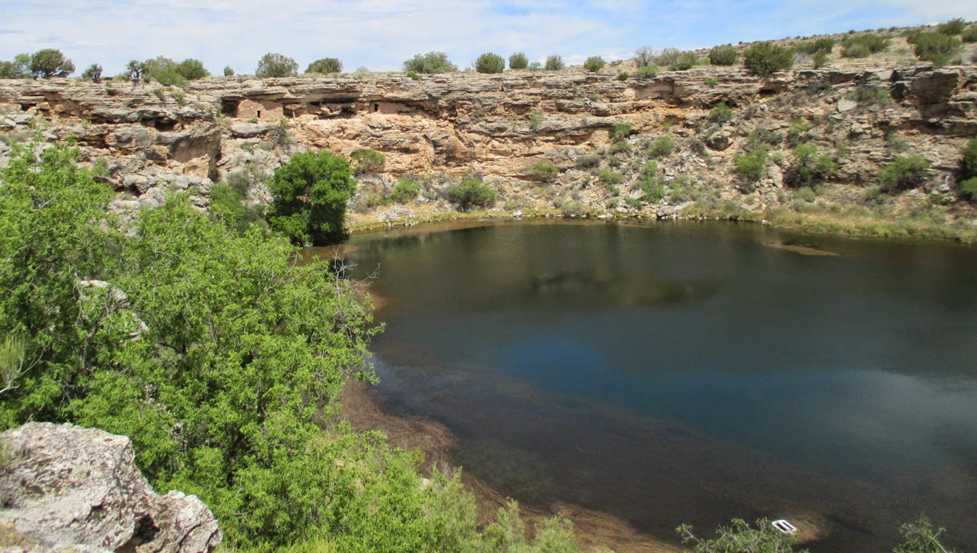 Ancient cliff dwelling is perched above the waters of an oasis desert sinkhole.