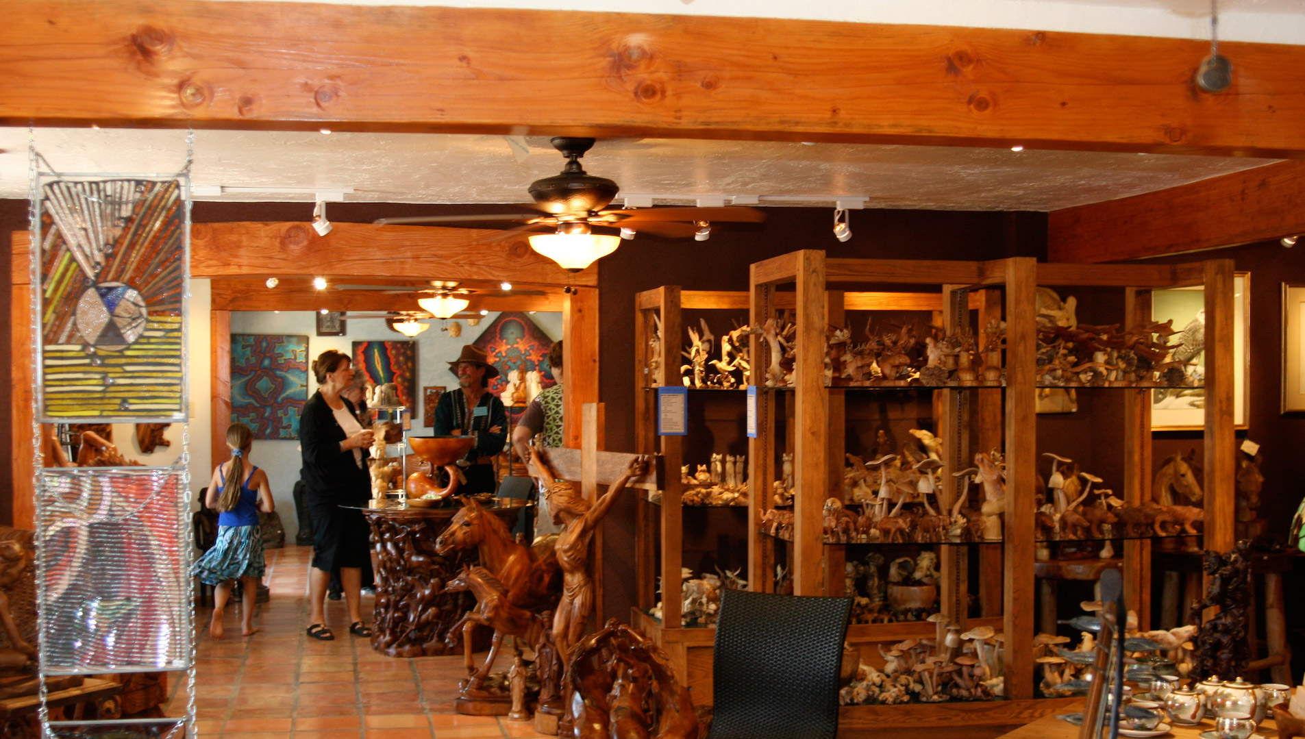 Teak wood carvings line the shelves inside Sacred Treasures.