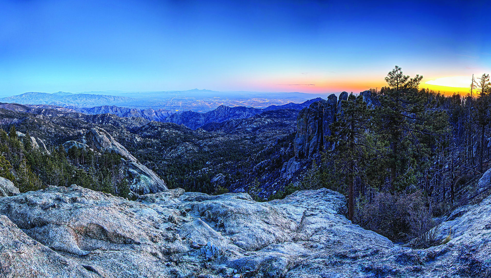 The granite gray summit of Mount Lemmon topped with vibrant colorful streaks across a cold morning sky.