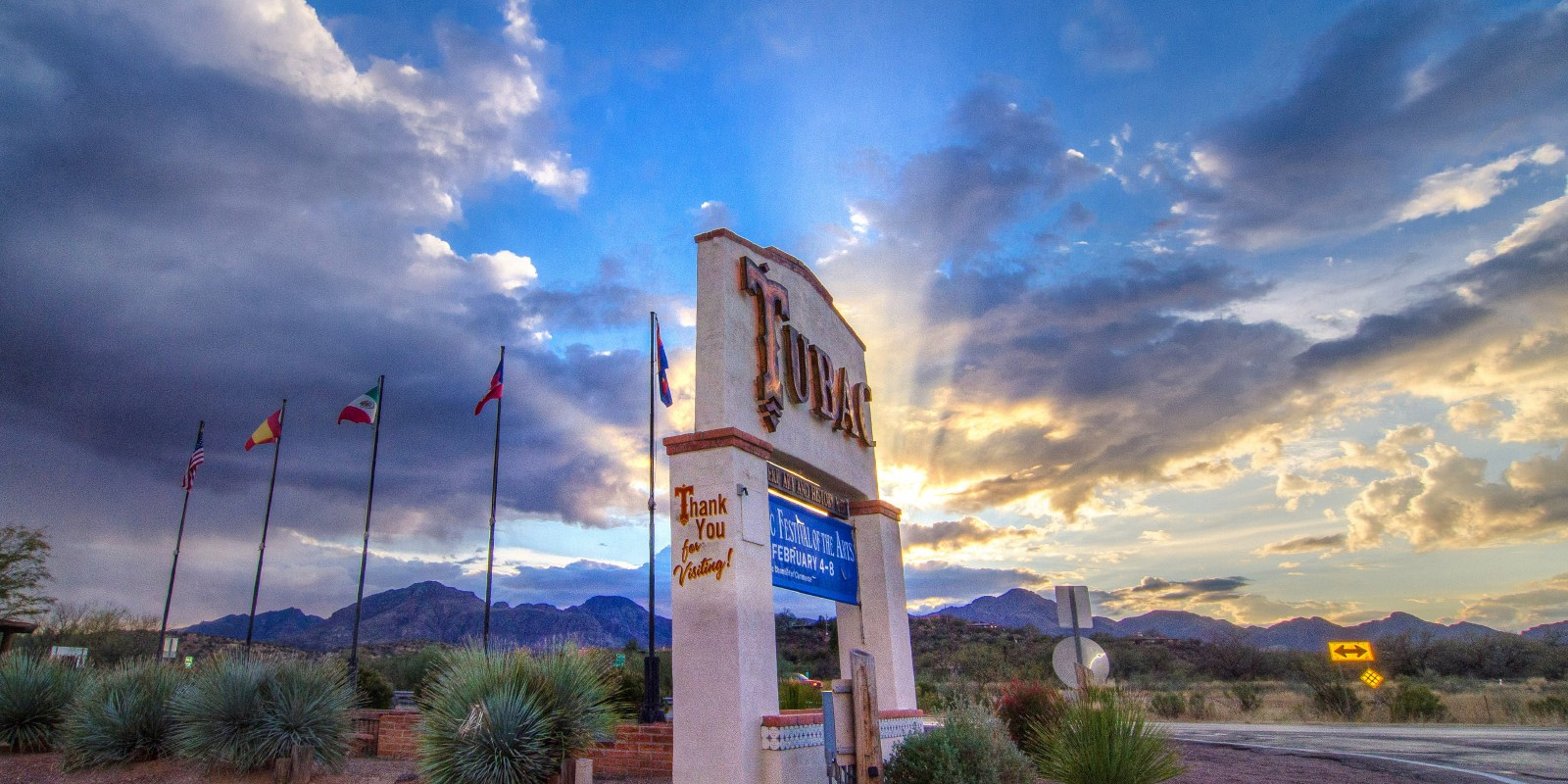Vibrant rays of the setting sun emerge from behind the clouds. In the foreground, a sign welcoming people to the village of Tubac, Arizona.