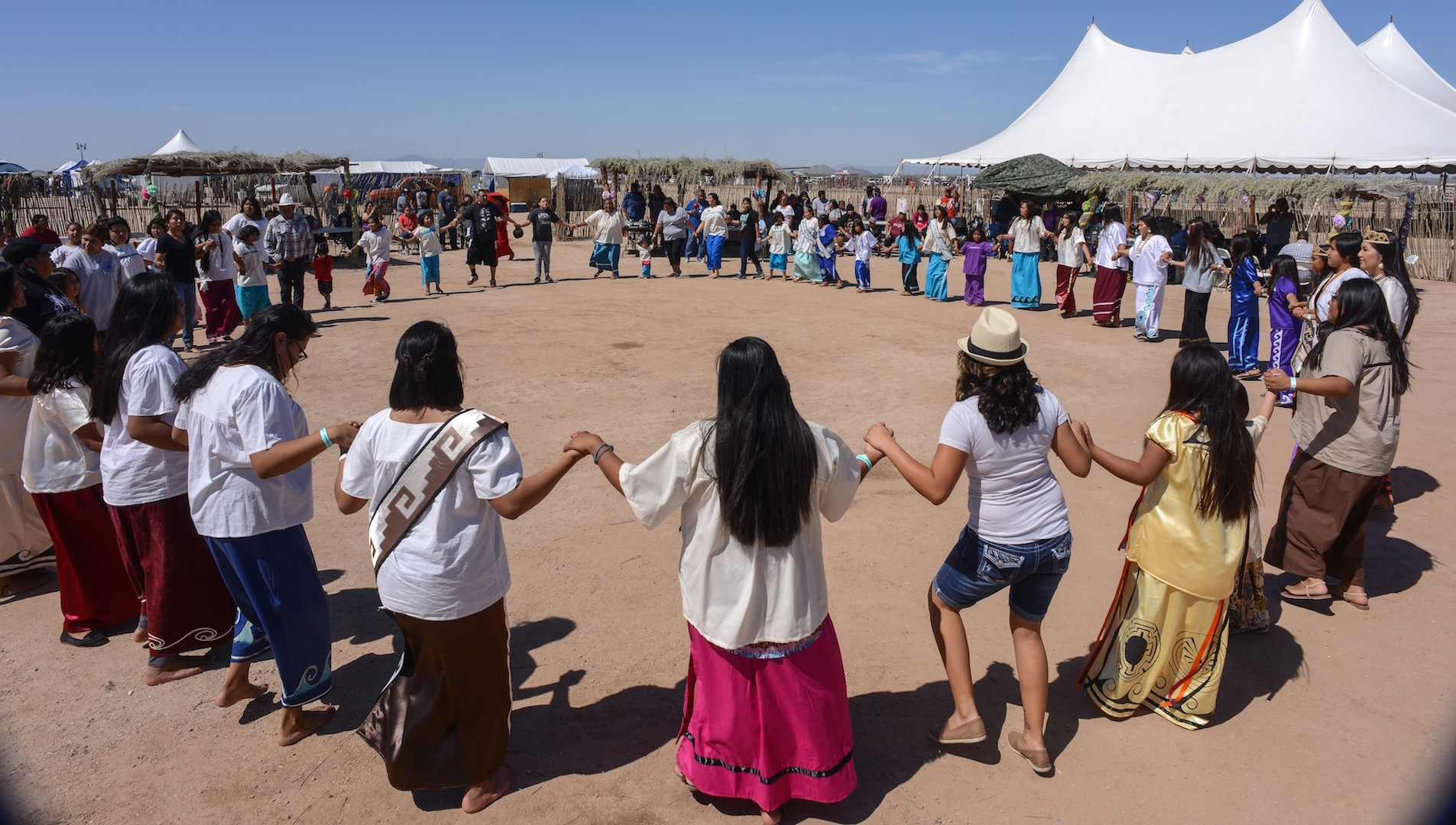 Dozens hold hands in a circle dance at a powwow on the Tohono O'Odham reservation.
