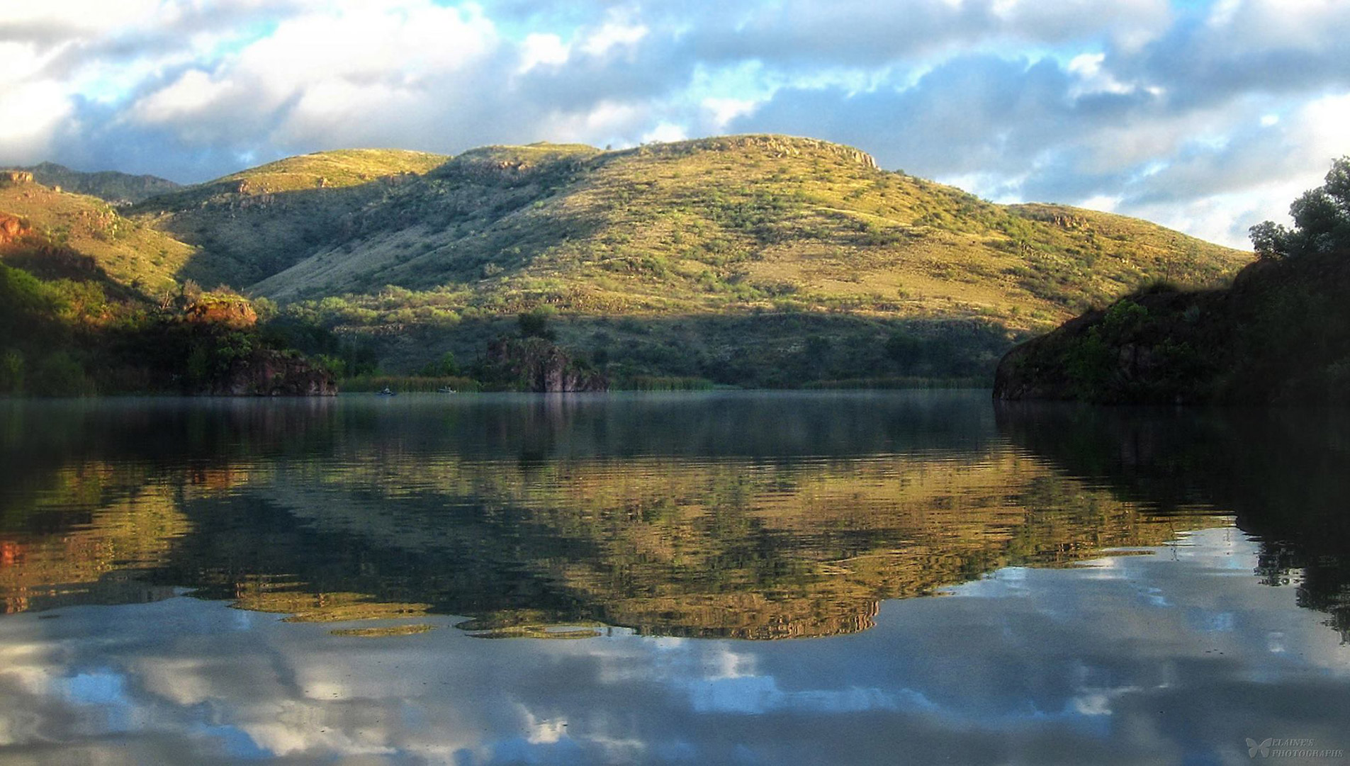 A reflection of the illuminated  hillside in the calm, still waters of Pena Blanca Lake.